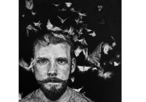 Black and white picture of a bearded man's head surrounded by dozens of butterflies in flight